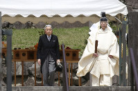 Japan's Emperor Akihito, left, is led by a Shinto priest, after visiting the tomb of his late father Hirohito to report his retirement at the Musashino Imperial Mausoleum in Tokyo, on April 23, 2019. (AP Photo/Koji Sasahara, Pool)