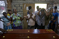 Relatives weep near the coffin with the remains of 12-year Sneha Savindi, who was a victim of Easter Sunday bombing at St. Sebastian Church, on April 22, 2019, in Negombo, Sri Lanka. (AP Photo/Gemunu Amarasinghe)