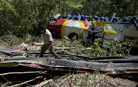 A park ranger examines the scene where a bus crashed head-on with another vehicle and plunged down a deep ravine, in Yolosa, Bolivia, on April 22, 2019. (AP Photo/Juan Karita)