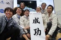 衝突実験に成功し、記念撮影に応じる佐伯孝尚・プロジェクトエンジニア(左から4人目)、澤田弘崇・はやぶさ2主任研究開発員(右端)ら=相模原市中央区で2019年4月5日、永山悦子撮影