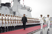 In this photo released by Xinhua News Agency, Chinese President Xi Jinping reviews an honor guard before boarding the destroyer Xining at a pier in Qingdao, east China's Shandong Province, on April 23, 2019. (Li Gang/Xinhua via AP)