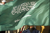 In this March 22, 2018 file photo, an Honor Guard member is covered by the flag of Saudi Arabia as Defense Secretary Jim Mattis welcomes Saudi Crown Prince Mohammed bin Salman to the Pentagon with an Honor Cordon, in Washington. (AP Photo/Cliff Owen)