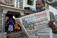 A man reads a newspaper with a lead story on Islamic State taking responsibility for the Easter Sunday terror attacks in Colombo, Sri Lanka, on April 24, 2019. (AP Photo/Gemunu Amarasinghe)