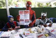 Electoral workers in superhero costumes show presidential ballot during the election at a polling station in Surabaya, Indonesia, on April 17, 2019. (AP Photo/Trisnadi)