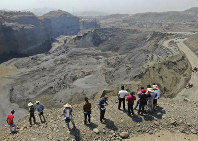 People stand atop a ridge overlooking the scene of a mudslide at a jade gemstone mining site on April 23, 2019, in Hpakant area of Kachin state, northern Myanmar. (Zaw Moe Htet via AP)