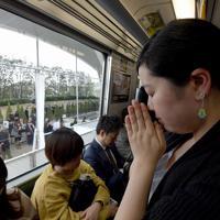 事故現場を通過する電車内で手を合わせる女性。14年前、女性の姉が通学で使っていた路線で、事故当日は脱線した電車より1本前の電車に乗っていた。女性は「当時、家族みんなで姉の心配をしたことを覚えている」と話した=兵庫県尼崎市で2019年4月25日午前9時16分、平川義之撮影