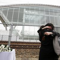 事故現場付近に設けられた献花台の前で抱き合う女性=兵庫県尼崎市で2019年4月25日午前9時32分、小出洋平撮影