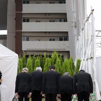 事故現場のマンションに向かって黙とうするJR西日本の来島達夫社長ら役員=兵庫県尼崎市で2019年4月25日午前9時18分(代表撮影)
