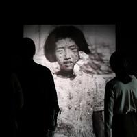 原爆投下3日後に毎日新聞記者の国平幸男さんが広島駅から爆心地に向かう途中に撮影した当時10歳の藤井幸子さんの写真が来館者を出迎える。別の場所に、被爆後の人生と20歳当時の幸子さんの写真が展示されている=広島市中区で2019年4月24日、山田尚弘撮影