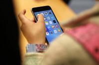 In this Sept. 25, 2015, file photo, a child holds an Apple iPhone 6S at an Apple store on Chicago's Magnificent Mile in Chicago. (AP Photo/Kiichiro Sato)