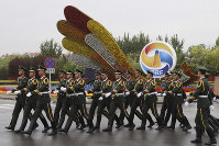 Chinese paramilitary policemen march past a decor for the Belt and Road Forum outside the special plane terminal of the Beijing International airport where foreign leaders are expected to arrive in Beijing, on April 24, 2019. (AP Photo/Ng Han Guan, Pool)