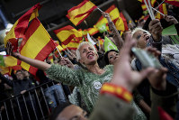 In this April 6, 2019 photo, supporters of Spain's far-right Vox Party wave Spanish and VOX flags during a party event in Leganes, on the outskirts of Madrid, Spain. (AP Photo/Bernat Armangue)