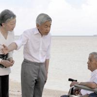 慰霊のために訪問された米自治領サイパン島の砂浜で、元日本兵から話を聞く前の天皇、皇后両陛下=サイパン島で2005年6月、代表撮影