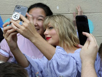Taylor Swift takes a selfie with a fan at an appearance at a butterfly mural in the Gulch in Nashville, Tenn., on April 25, 2019. (Alan Poizner/The Tennessean via AP)