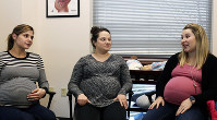 In this Jan. 29, 2019, photo provided by Mountain Area Health Education Center, from left, Hayley Heninger, Morgan Shirley and Kailee Morel Alvarez share their pregnancy experiences during a prenatal session at Mountain Area Health Education Center in Asheville, N.C. (Brenda Benik via AP)