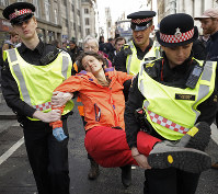 Police remove an Extinction Rebellion climate change protester who blocked a road outside the Goldman Sachs office in the City of London, on April 25, 2019. (AP Photo/Matt Dunham)