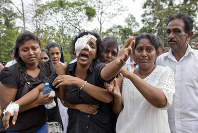 In this April 24, 2019 file photo, Anusha Kumari, center, weeps during a mass burial for her husband, two children and three siblings, all victims of Easter Sunday's bomb attacks, in Negombo, Sri Lanka. (AP Photo/Gemunu Amarasinghe)