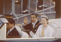 Emperor Akihito and Empress Michiko wave to well-wishers during a parade from the Imperial Palace in Tokyo's Chiyoda Ward to the Akasaka Palace in Minato Ward after his official enthronement ceremony on Nov. 12, 1990. (Mainichi/Katsumi Takahashi)