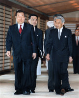 Emperor Akihito guides South Korean President Kim Dae-jung, who was officially visiting Japan, at the Imperial Palace in Tokyo on Oct. 7, 1998. (Pool photo)
