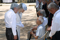 Emperor Akihito and Empress Michiko speak to Kiyokazu Tsuchida, a former Japanese soldier who survived the battle of Peleliu Island in 1944, in front of a cenotaph for victims of World War II, on the Pacific island of Palau on April 9, 2015. (Pool photo)