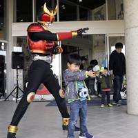 仮面ライダー「クウガ」と記念撮影する少年。カメラを構える母に向かって得意のポーズ=宮城県石巻市の石ノ森萬画館で