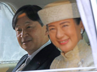 Crown Prince Naruhito and Crown Princess Masako enter the Imperial Palace by car to attend the