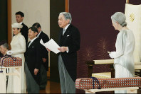 Emperor Akihito, center, reads his final statement, watched by Empress Michiko, right, at the