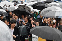 Crowds of people watch a big-screen live broadcast of Emperor Akihito's abdication on a street in Tokyo's Shinjuku Ward, on April 30, 2019. (Mainichi/Toshiki Miyama)