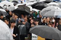 Crowds of people watch a big-screen live broadcast of Emperor Akihito's abdication on a street in Tokyo's Shinjuku Ward, on April 30, 2019. (Mainichi/Toshiki Miyama)