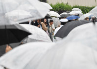 Crowds of people endure rain to watch a live broadcast of Emperor Akihito's abdication ceremony on a big screen on a street in Tokyo's Shinjuku Ward, on April 30, 2019. (Mainichi/Toshiki Miyama)