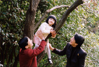 Princess Aiko climbs a tree while being supported by Crown Prince Naruhito, left, and Crown Princess Masako at their residence in Togu Palace on Nov. 17, 2004. (Photo courtesy of the Imperial Household Agency)