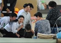 Crown Prince Naruhito, third from left, and Crown Princess Masako, second from left, speak to survivors of the March 2011 Great East Japan Earthquake at an evacuation center in the city of Yamamoto, Miyagi Prefecture, on June 4, 2011. (Pool photo)