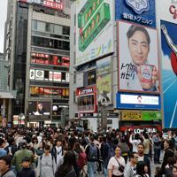 道頓堀では天皇陛下の最後のおことばを伝える映像が大型モニター(左奥)に映し出された=大阪市中央区で2019年4月30日午後5時8分、木葉健二撮影