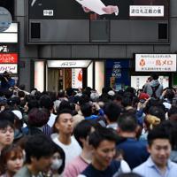 道頓堀では天皇陛下の最後のおことばを伝える映像が大型モニターに映し出された=大阪市中央区で2019年4月30日午後5時7分、木葉健二撮影