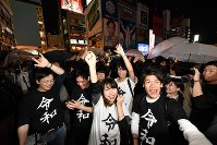 People celebrate the beginning of the Reiwa era at 12 a.m. on May 1, 2019, in Osaka's Chuo Ward. Their T-shirts are emblazoned with the kanji characters for Reiwa. (Mainichi/Naohiro Yamada)