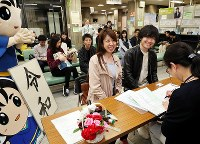 A couple smile as they submit their marriage registration at 12 a.m. on May 1, 2019, at a special desk set up for people wishing to wed in the first hours of the Reiwa era, at the municipal office in Hirakata, Osaka Prefecture. (Mainichi/Kentaro Ikushima)