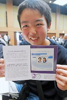 A boy smiles as he shows off a stamp commemorating the June 9, 1993 marriage of then Crown Prince Naruhito and Crown Princess Masako that he had stamped with the date May 1, Reiwa 1 (2019), the day the couple become Emperor and Empress to commence the Reiwa era, at the Tokyo Central Post Office. (Mainichi/Motohiro Negishi)
