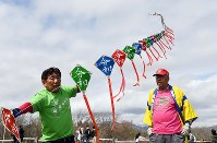 Mitsuo Tanaka, left, flies his string of kites all emblazoned with the new Reiwa era name in Sapporo's Toyohira Ward on May 1, 2019. (Mainichi/Kan Takeuchi)