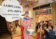 People smile at the bespectacled clown Kuidaore Taro, one of Osaka's most famous icons, wishing passers-by a happy Reiwa era, in Osaka's Chuo Ward on May 1, 2019. (Mainichi/Maiko Umeda)