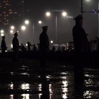 平成最後の瞬間を迎える人たちが続々と集まる中、皇居前広場で警備をする警察官たち=東京都千代田区で2019年4月30日午後11時10分、宮間俊樹撮影