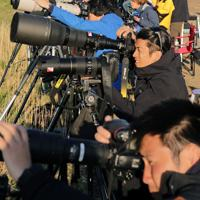 打ち上げられた小型ロケット「MOMO3号機」にカメラを向ける報道陣ら=北海道大樹町で2019年5月4日午前5時45分、貝塚太一撮影