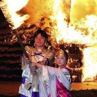 燃え上がる産屋の前でたいまつを掲げる主役の男女=埼玉県行田市埼玉のさきたま古墳公園で