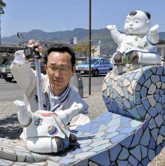 頭部が壊された唐子人形を調べる市職員=佐賀県伊万里市で2019年5月7日11時1分