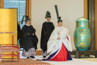 In this photo released by Imperial Household Agency of Japan, Japan's Emperor Naruhito, right, attends a ritual of dispatching imperial envoys to the Ise Grand Shrine, and mausoleums of the late emperors to report the date of his Enthronement Ceremony, at the Imperial Palace in Tokyo, on May 8, 2019. (Imperial Household Agency of Japan via AP)