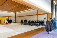 In this photo released by Imperial Household Agency of Japan, Japan's Emperor Naruhito, left, attends a ritual of dispatching imperial envoys to the Ise Grand Shrine, and mausoleums of the late emperors to report the dates of his enthronement ceremonies, at the Imperial Palace in Tokyo, on May 8, 2019. (Imperial Household Agency of Japan via AP)