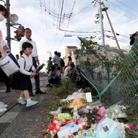 事故現場に花を供える親子=大津市で2019年5月8日午後5時25分、幾島健太郎撮影