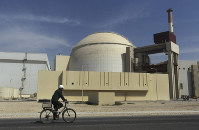 In this Oct. 26, 2010 file photo, a worker rides a bike in front of the reactor building of the Bushehr nuclear power plant, outside Bushehr, Iran. (AP Photo/Majid Asgaripour/Mehr News Agency)