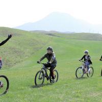 阿蘇外輪山の標高約800メートルにある牧野で楽しむマウンテンバイクツアー=熊本県阿蘇市で2019年4月22日午後3時10分、杉山恵一撮影