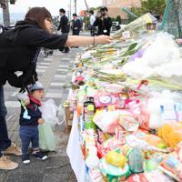 保育園児たちが事故にあった現場に花を供える親子=大津市で2019年5月9日午前10時25分、梅田麻衣子撮影