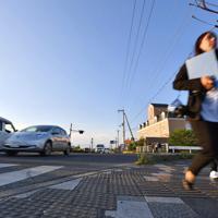 たくさんの自動車が行き交う事故現場。正面の交差点から段差のないところ(手前)に軽乗用車が突っ込んできたとみられる=大津市で2019年5月9日午後6時7分、猪飼健史撮影
